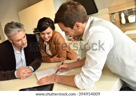 Couple choosing kitchen furniture and getting quotation - stock photo