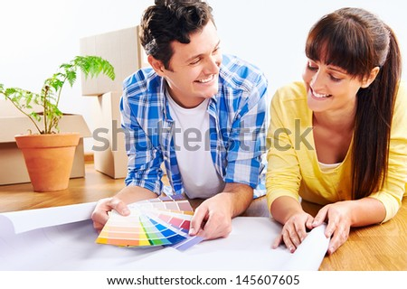 couple choosing paint colour from swatch in new home apartment together