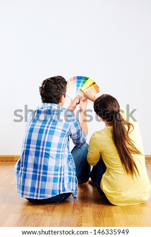 couple choosing paint swatch for new home - stock photo