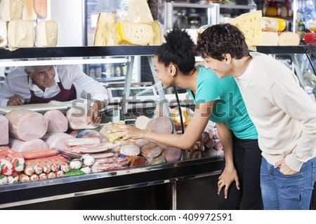 Couple Choosing Product From Display Cabinet While Salesman Assi - stock photo