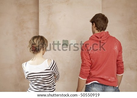 Couple choosing sample paint colours on wall, back view - stock photo