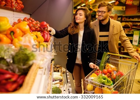 Couple choosing vegetables in a grocery store  - stock photo