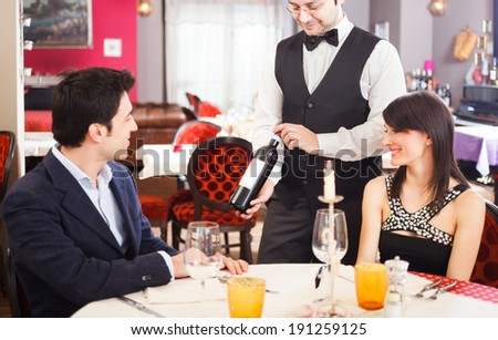 Couple choosing wine while having dinner in a restaurant - stock photo