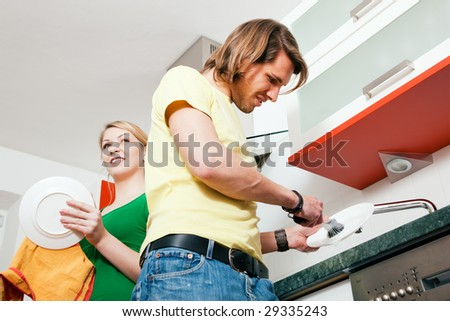 Couple cleaning their dishes in a kitchen sink