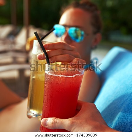 Couple clinking glasses with cocktails at poolside - stock photo