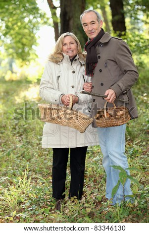 Couple collecting wild mushrooms