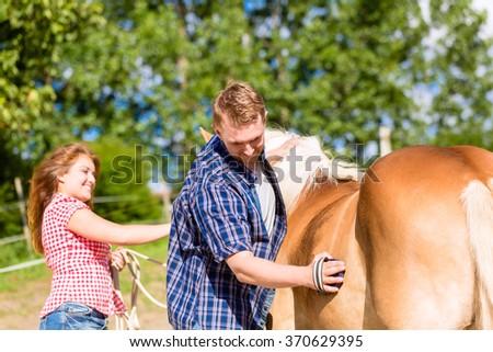 Couple combing horse on pony farm - stock photo