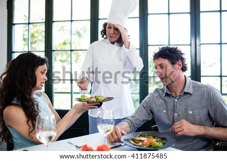 Couple complaining about the food to chef in a restaurant - stock photo