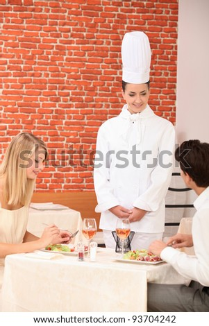 Couple complimenting the chef on her cooking - stock photo