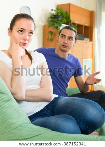 Couple conflict. Portrait of girl with her boyfriend after quarrel in living room 