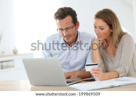Couple connected with laptop and shopping online - stock photo