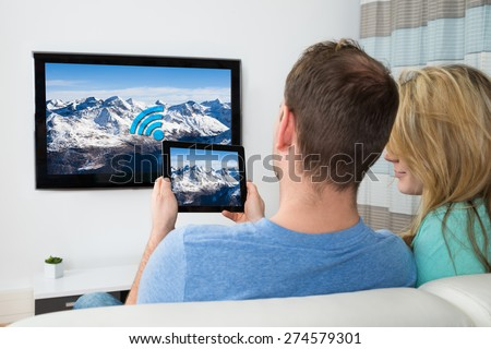 Couple Connecting Television Channel Through Wifi On Digital Tablet - stock photo