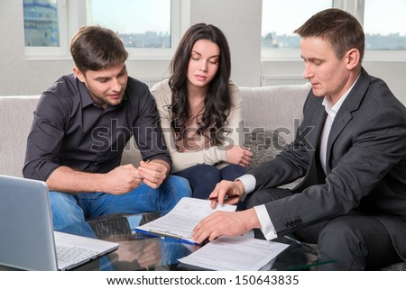 couple consults with agent, signing paperwork - stock photo