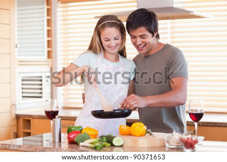 Couple cooking dinner while drinking red wine in their kitchen - stock photo