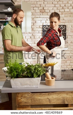 Couple cooking in kitchen, man tieing woman's apron.