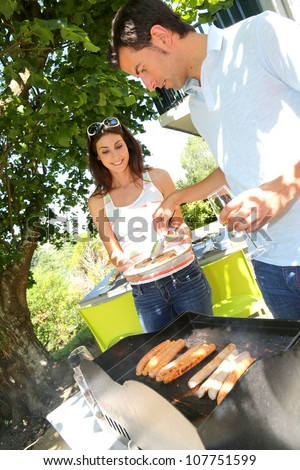 Couple cooking meat on barbecue grill - stock photo