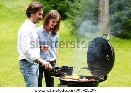 couple cooking on grill outdoors - stock photo