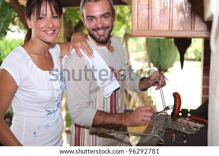 Couple cooking sausages on the barbecue - stock photo