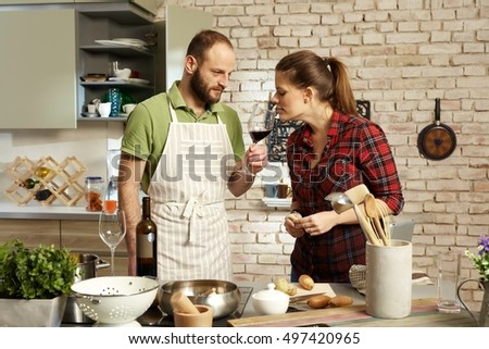 Couple cooking together, tasting wine.