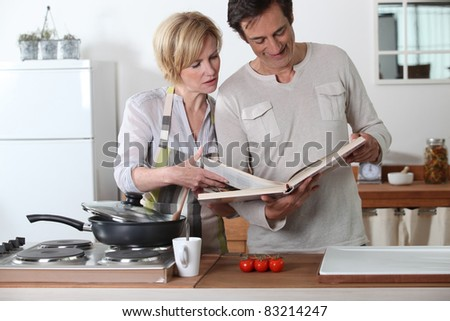 Couple cooking together with a recipe book - stock photo