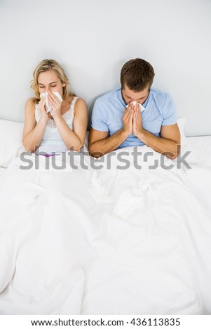 Couple covering nose while sneezing on bed in bedroom