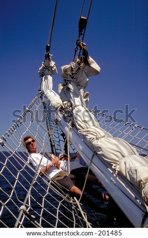 Couple cruising on bowsprit of sailing yacht, Coral Sea, Great Barrier Reef, Australia