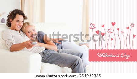 Couple cuddling while watching TV against valentines graphic - stock photo