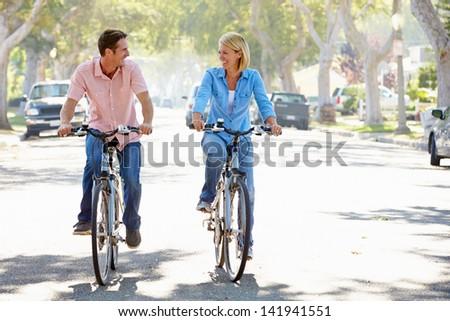 Couple Cycling On Suburban Street - stock photo