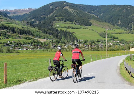 Couple cycling through the valley of the Austrian Alps - stock photo