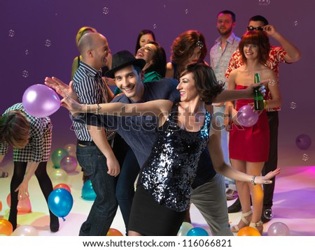 couple dancing and smiling, together with friends, on colored backgrpund, with bubbles and balloons