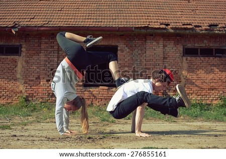 Couple dancing breakdance on the street - stock photo