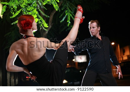 Couple dancing hot latin dance on a street at night - stock photo