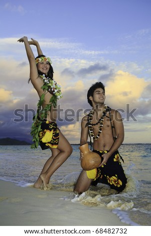couple dancing hula by the ocean in hawaii - stock photo