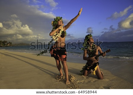 couple dancing hula on the beach at sunrise with the man playing ukulele - stock photo