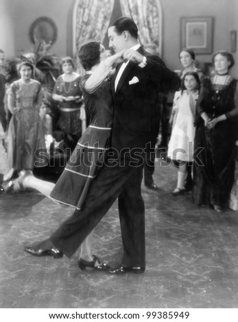 Couple dancing lightly while others are watching - stock photo