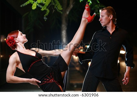 Couple dancing on a street at night. - stock photo