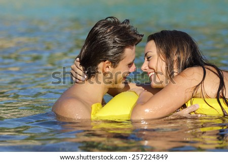 Couple dating and kissing with love in summer vacation on the beach while bathing in the water - stock photo