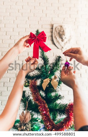 Couple decorating Christmas tree. Hands of two holding decorative ball and bow near green pine-tree branch. Holiday, happy family, party concept