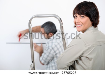 Couple decorating home - stock photo