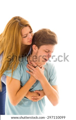 Couple demonstrating first aid procedure for abdominal thrusts, Heimlich Manoeuvre or Maneuver to treat man choking by foreign objects - stock photo