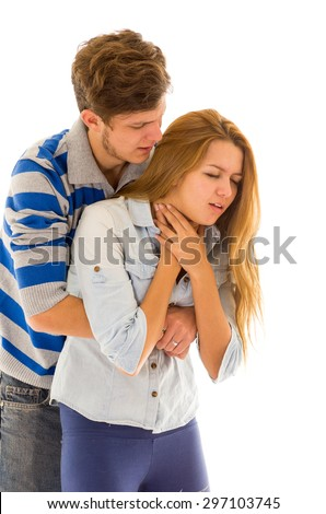 Couple demonstrating first aid techniques by man performing heimlich on female choking. - stock photo