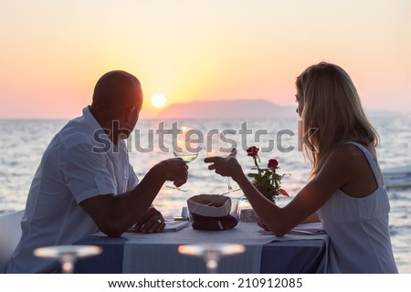 Couple dining in sea restaurant at sunset
