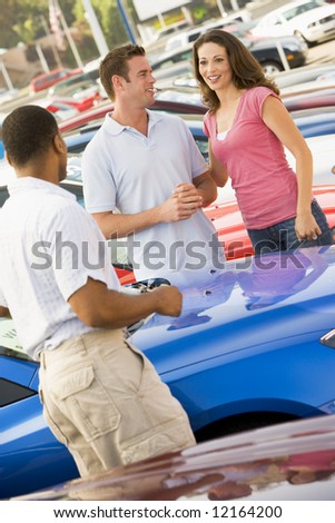 Couple discussing new car with salesman on lot - stock photo
