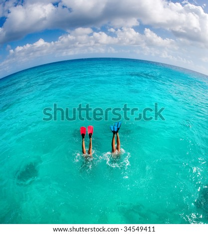 couple dive snorkeling with flippers showing on honeymoon vacation - stock photo