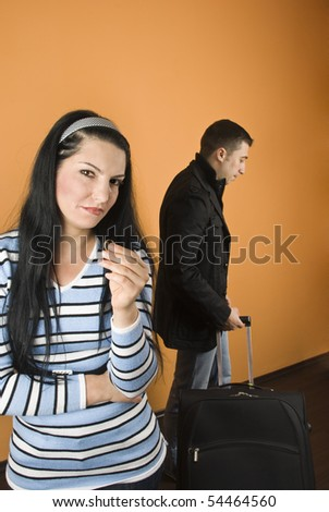 Couple divorce,woman  crying  and stand with arms crossed and holding the wedding ring while the man leaves home - stock photo