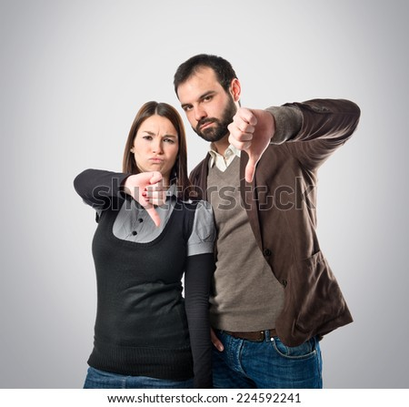 Couple doing bad signal over grey background - stock photo