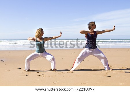 Couple doing chi kung on the beach - stock photo