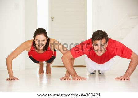 Couple doing push-ups in home gym - stock photo