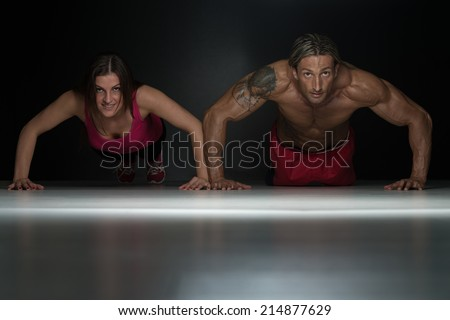 Couple Doing Pushups As Part Of Bodybuilding Training In A Studio - stock photo