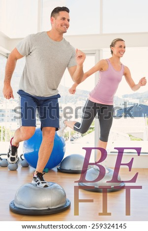 Couple doing step aerobics in fitness studio against be fit - stock photo